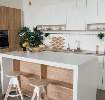 white kitchen with wooden accents and kitchen island with storage